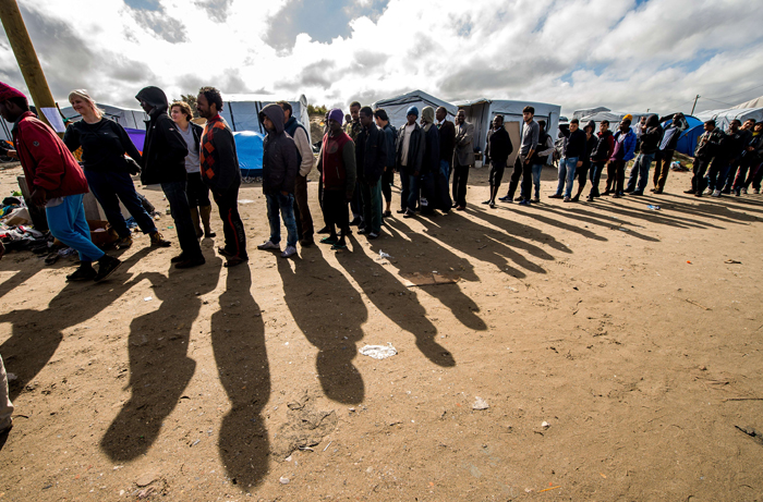 "Migrants queue to get food Tuesday at a site in Calais dubbed the ""New Jungle"", where some 3,000 people have set up camp. The slum-like migrant camp sprung up after the closure of notorious Red Cross camp Sangatte, which had become overcrowded and prone to violent riots. However migrants and refugees have kept coming and the ""New Jungle"" has swelled along with the numbers of those making  often deadly attempts to smuggle themselves across the Channel. (PHILIPPE HUGUEN/AFP/Getty Images)"