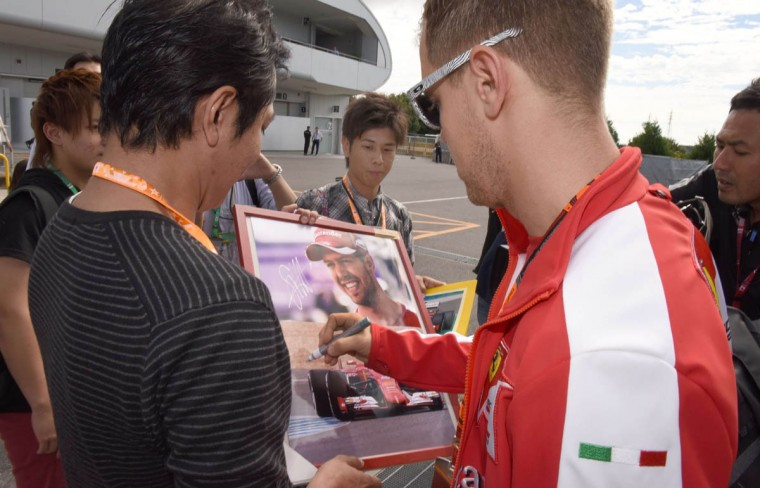 Ferrari driver Sebastian Vettel (Right) of Germany signs autographs for his fans before the third practice session ahead of the Formula One Japanese Grand Prix in Suzuka on September 26, 2015. (Toru Yamanaka/Getty Images)