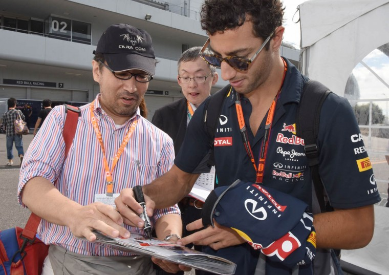 Red Bull driver Daniel Ricciardo (Right) of Australia signs autographs for his fans before the third practice session ahead of the Formula One Japanese Grand Prix in Suzuka on September 26, 2015. (Toru Yamanaka/Getty Images)