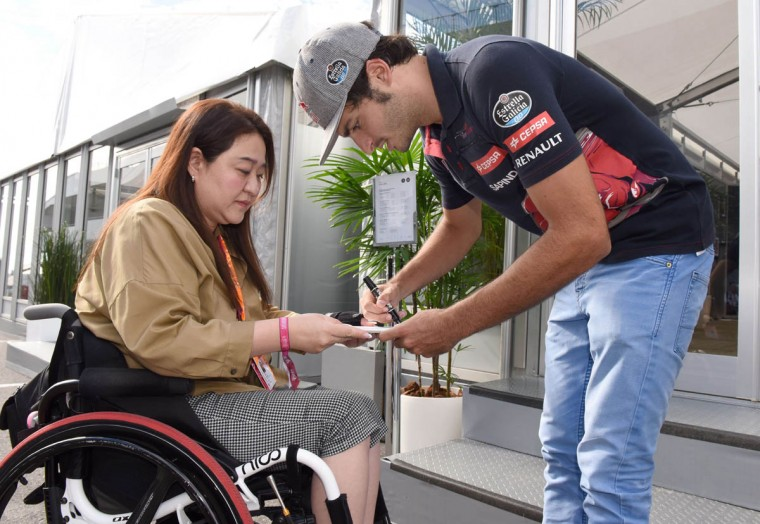 Toro Rosso driver Carlos Sainz Jr (Right) of Spain signs an autograph for a fan before the third practice session ahead of the Formula One Japanese Grand Prix in Suzuka on September 26, 2015. (Toru Yamanaka/Getty Images)