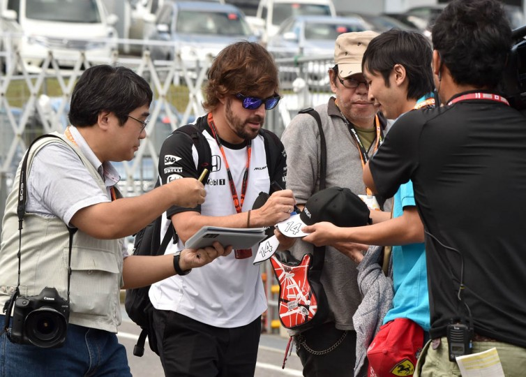 McLaren driver Fernando Alonso of Spain signs autographs for Japanese fans at the paddock before the third practice session of the Formula One Japanese Grand Prix at the Suzuka circuit on September 26, 2015. (Kazuhiro Nogi/Getty Images)