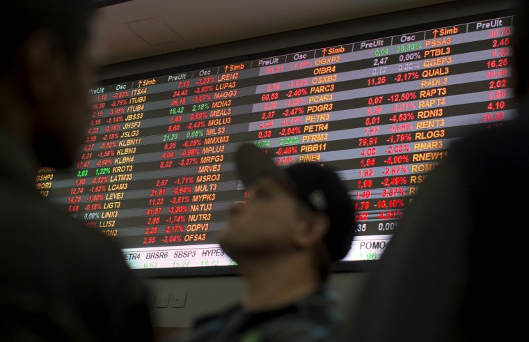 """Visitors look at stock price monitors inside the BM&F BOVESPA stock exchange headquarters in Sao Paulo, Brazil, Thursday, Sept. 10, 2015. Brazil's financial markets fell Thursday in the aftermath of credit agency Standard & Poor's downgrading the country's sovereign debt to """"junk"""" status. (AP Photo/Andre Penner)"""