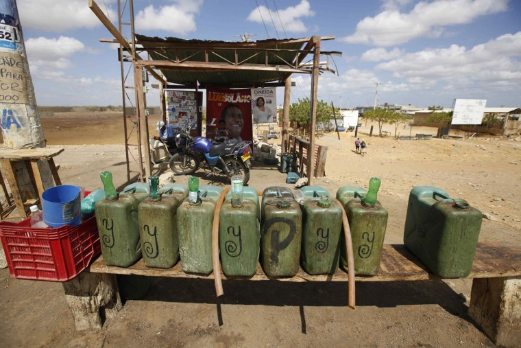 """Containers of gas sit at Victor Gonzalez's make-shift service station in Uribia, Colombia, Thursday, Sept. 10, 2015, near the border with Venezuela. Gonzalez is one of many """"pimpineros,"""" salespeople who buy gas from middlemen who purchase it cheaply in Venezuela, and sell it to commuters in Colombia at closer to retail price. Gonzalez says he used to charge clients about $5 dollars per gallon before Venezuelan President Nicolas Maduro closed the border. Now he pumps it out to clients willing to pay double. (AP Photo/Fernando Vergara)"""