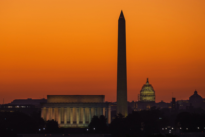 The orange sky of sunrise is captured behind the skyline of Washington on Tuesday, the first day back to work for the U.S. Congress after their summer recess. (J. David Ake/AP)