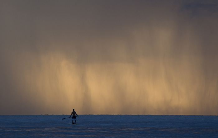 Pablo Dona of Miami pauses while paddleboarding as sheets of rain fall on Tuesday off the shores of Bal Harbour, Fla. (Wilfredo Lee/AP)