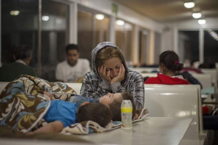 In this photo taken on Wednesday, Sept. 9, 2015 a refugee sleeps with her children on a ferry traveling from the northeastern Greek island of Lesbos to the Athens' port of Piraeus. Greece's caretaker government chartered two extra ferries and sent additional staff to Lesbos to speed up the registration and ease overcrowding on the island, where more than 20,000 refugees and migrants had been living in precarious conditions after arriving on dinghies from the nearby Turkish coast. (AP Photo/Santi Palacios)