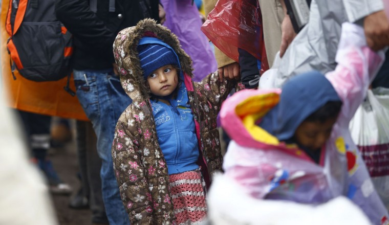 A young girl holding her mother's hand waits in a queue for a bus that will take them to the center for asylum seekers near Roszke, southern Hungary in Roszke, Thursday, Sept. 10, 2015. Leaders of the United Nations refugee agency warned Tuesday that Hungary faces a bigger wave of 42,000 asylum seekers in the next 10 days and will need international help to provide shelter on its border. (AP Photo/Matthias Schrader)