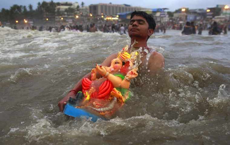 A devotee carries an idol of Hindu elephant headed god Ganesha to immerse it in the Arabian Sea during Ganesh Chaturthi festival celebrations in Mumbai, India, Monday, Sept. 21, 2015. The festival is celebrated as the birthday of Ganesha, the Hindu god of wisdom, prosperity and good fortune. (AP Photo/Rafiq Maqbool)