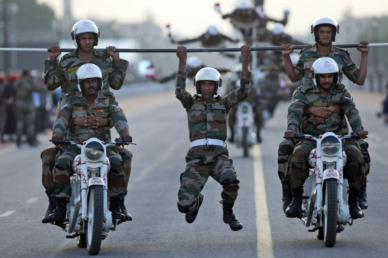 Indian army soldiers perform a daredevil motorcycle stunt during a parade to mark the 50th anniversary of the India-Pakistan war of 1965, in New Delhi, India, Sunday, Sept. 20, 2015. The parade concluded celebrations to honor soldiers who fought the war in 1965. (AP Photo/Tsering Topgyal)