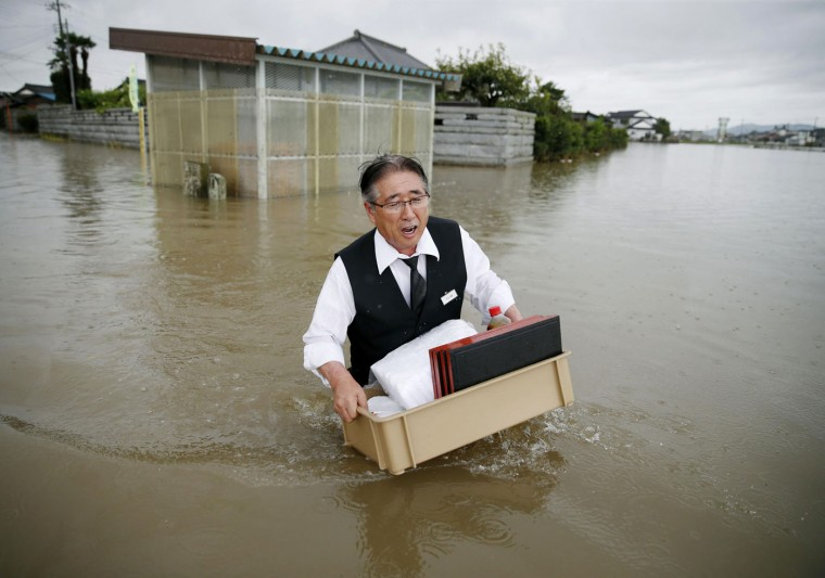 A man carries belongings through a flooded street in Oyama, Tochigi prefecture, northeast of Tokyo Thursday, Sept. 10, 2015. Heavy rain is pummeling Japan for a second straight day, overflowing rivers and causing landslides and localized flooding in the eastern part of the country. (Kyodo News via AP)