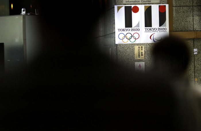 Visitors frame the logo of Tokyo Olympic Games 2020 at the Tokyo Metropolitan Government building in Tokyo on Tuesday. Tokyo Olympic organizers on Tuesday decided to scrap the logo for the 2020 Games following another allegation its Japanese designer might have used copied materials. (Eugene Hoshiko/AP)