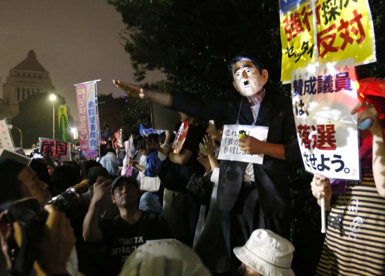 A protester wearing a mask of Japanese Prime Minister Shinzo Abe gestures during a rally against Japanese government in front of the parliament building in Tokyo, Friday, Sept. 18, 2015. Japan's parliament is moving toward final approval of legislation that would loosen post-World War II constraints placed on its military, an issue that has sparked sizeable street protests and raised fundamental questions about whether the nation needs to shift away from its pacifist ways to face growing security challenges.  || CREDIT: SHUJI KAJIYAMA - AP PHOTO