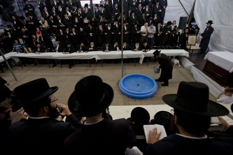 """Ultra-Orthodox Jewish men surround a portable swimming pool with goldfish as they participate in a Tashlich ceremony in the ultra-Orthodox city of Bnei Brak , near Tel Aviv, Israel, Sunday, Sept. 20, 2015. Tashlich, which means """"to cast away"""" in Hebrew, is the practice in which Jews go to a large flowing body of water and symbolically """"throw away"""" their sins by throwing a piece of bread, or similar food, into the water before the Jewish holiday of Yom Kippur, which starts at sundown Tuesday. (AP Photo/Ariel Schalit)"""