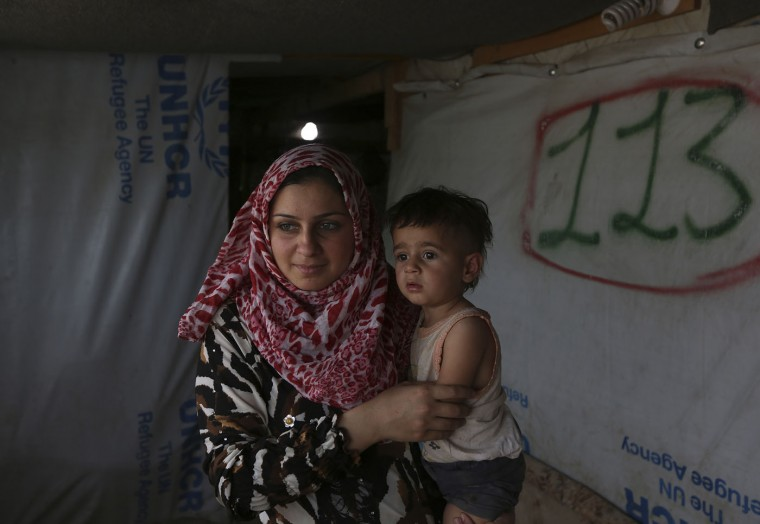 Syrian refugee Khitam, 21, holds her 18-month-old daughter Reeham inside her tent at a Syrian refugee camp in the town of Deir Zanoun, Bekaa Valley, Lebanon, The UNHCR has said there are about 1,150,000 Syrian refugees registered in Lebanon, equal to a quarter of Lebanon's own population of 4.5 million. Beirut estimates there are another 500,000 unregistered Syrians in the country. (AP Photo/Bilal Hussein)