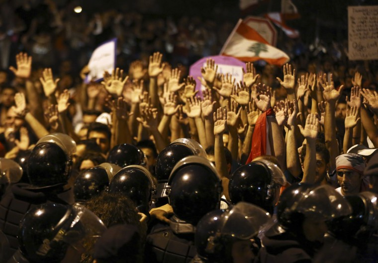 Lebanese anti-government protesters raise their hands as Lebanese riot policemen stand guard and block a road leading to the parliament building during a protest against the on-going trash crisis and government corruption, in Beirut, Lebanon, Sunday, Sept. 20, 2015. Hundreds of Lebanese protesters pushed through a security cordon as they marched toward parliament on Sunday, the latest in a series of demonstrations that began with a trash crisis but has since expanded to target the country's political class. (AP Photo/Bilal Hussein)