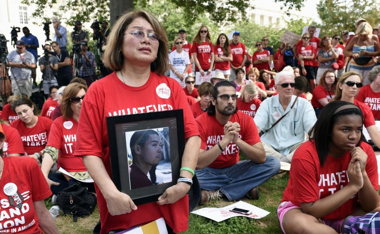 Maria Pike of Chicago, holding a photo of her son Ricky Pike, attends a rally against gun violence, Thursday, Sept. 10, 2015, on Capitol Hill in Washington. The father of Virginia shooting victim Alison Parker is urging lawmakers to defy the powerful gun lobby and pass legislation to strengthen background checks for gun purchasers. (AP Photo/Susan Walsh)