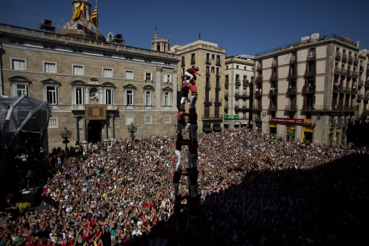 """Members of the Castellers Joves Xiquets de Valls form a human tower or """"Castellers"""" during the Saint Merce celebrations in San Jaime square in Barcelona, Spain, Sunday, Sept. 20, 2015. The tradition of building human towers or """"castells"""" dates back to the 18th century and takes place during festivals in Catalonia, where """"colles"""" or teams compete to build the tallest and most complicated towers. A """"castell"""" is considered completely successful when it is loaded and unloaded without falling apart. In 2010 """"castells"""" were declared by UNESCO one of the Masterpieces of the Oral and Intangible Heritage of Humanity. (AP Photo/Emilio Morenatti)"""