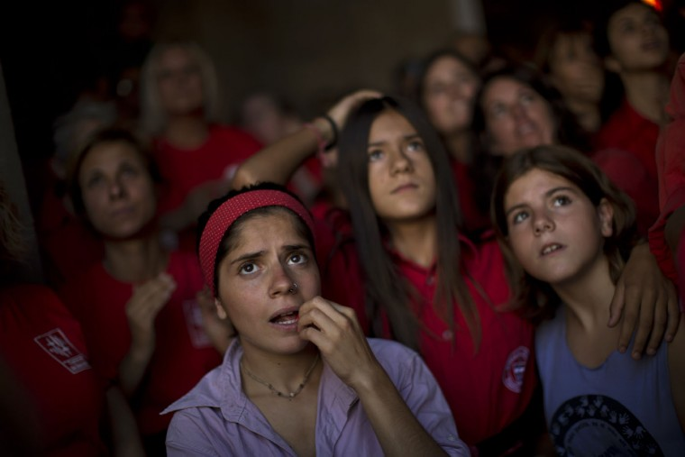 """Members of different Castellers watch as """"Joves Xiquets de Valls"""" form a human tower or """"Castellers"""" during the Saint Merce celebrations in San Jaime square in Barcelona, Spain, Sunday, Sept. 20, 2015. The tradition of building human towers or """"castells"""" dates back to the 18th century and takes place during festivals in Catalonia, where """"colles"""" or teams compete to build the tallest and most complicated towers. A """"castell"""" is considered completely successful when it is loaded and unloaded without falling apart. In 2010 """"castells"""" were declared by UNESCO one of the Masterpieces of the Oral and Intangible Heritage of Humanity. (AP Photo/Emilio Morenatti)"""