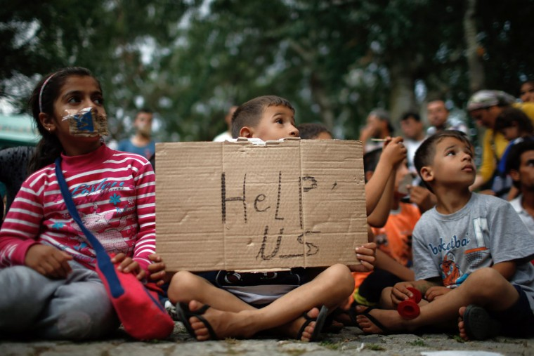 A child holds up a sign as migrants stage a protest in a stadium used for traditional Kirkpinar Oil Wrestling as they wait to walkdown a highway towards Turkeyís western border with Greece and Bulgaria, in Edirne, Turkey, Monday, Sept. 21, 2015. The migrants were stopped Friday by Turkish law enforcement on a highway near the city of Edirne, causing a massive traffic jam. (AP Photo/Emrah Gurel)
