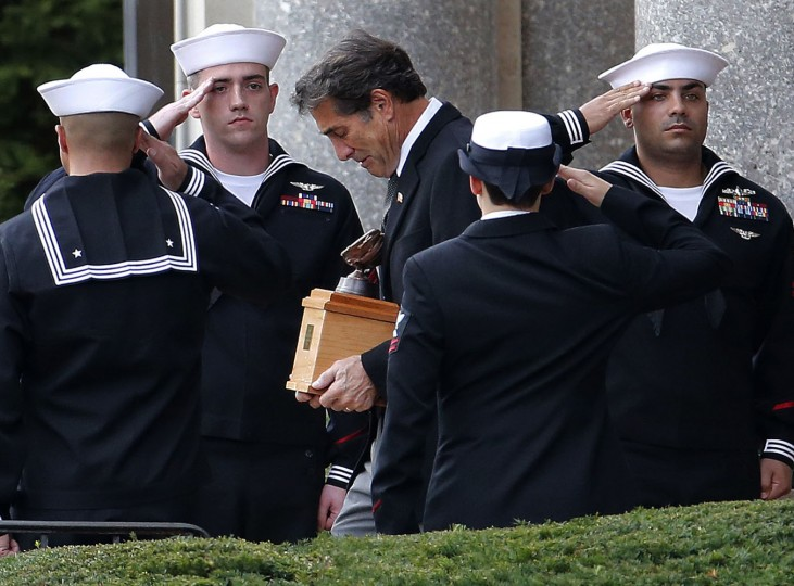 United States Navy officers salute as Tim Berra, center right, son of New York Yankees Hall of Fame catcher Yogi Berra, carries his father's remains in an urn following funeral services at Church of the Immaculate Conception, Tuesday, Sept. 29, 2015, in Montclair, N.J. The baseball legend known for his quirky sayings died Sept. 22. He was 90. (AP Photo/Julio Cortez)