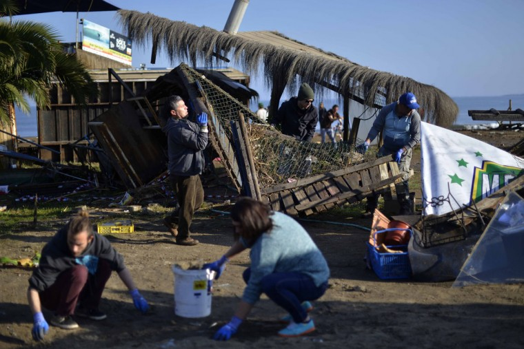 People clean the beach after an earthquake-triggered tsunami damaged homes and businesses in Concon, Chile, Thursday, Sept. 17, 2015. Several coastal towns were flooded from small tsunami waves set off by late Wednesday's magnitude-8.3 earthquake, which shook the Earth so strongly that rumbles were felt across South America. (AP Photo/Matias Delacroix)