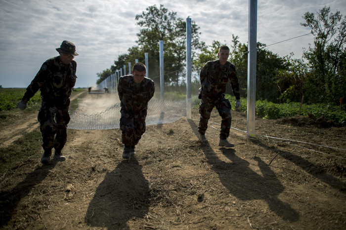 Hungarian soldiers work to construct a temporary fence on the border between Hungary and Croatia to prevent migrants from crossing the border line at Beremend, some 140 miles south of Budapest, Hungary, on Tuesday. (Tamas Soki/MTI via AP)