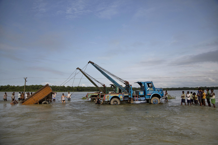 Tow trucks pull a vehicle that was swept off after it tried to cross a flooded road at Pobitora village, about 34 miles east of Gauhati, India, on Tuesday. Monsoon floods have inundated hundreds of villages across the northeast Indian state of Assam, killing several people and forcing some 800,000 people to leave their homes. (Anupam Nath/AP)