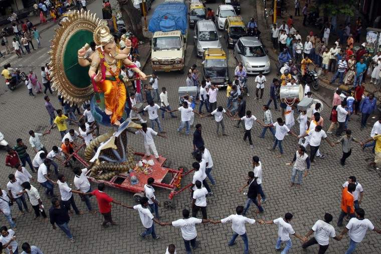 Devotees transport an idol of elephant headed Hindu god Ganesha from a workshop to a worship venue ahead of the Ganesh Chaturthi festival in Mumbai, India, Sunday, Sept. 13, 2015. After worshipping during the ten day long festival, the idol will be immersed in the Arabian Sea. (AP Photo/Rajanish Kakade)