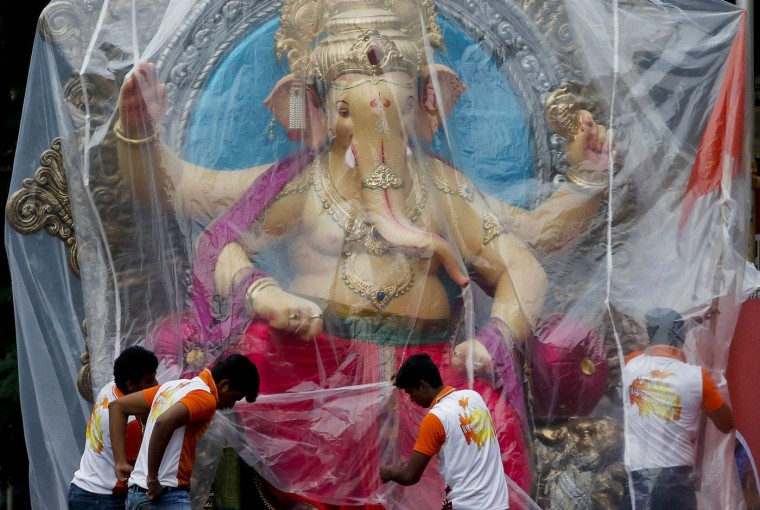 Devotees cover an idol of elephant headed Hindu god Ganesha with a plastic sheet at a workshop before shifting the same to a worship venue ahead of the Ganesh Chaturthi festival in Mumbai, India, Sunday, Sept. 13, 2015. After worshipping during the ten day long festival, the idol will be immersed in the Arabian Sea. (AP Photo/Rajanish Kakade)
