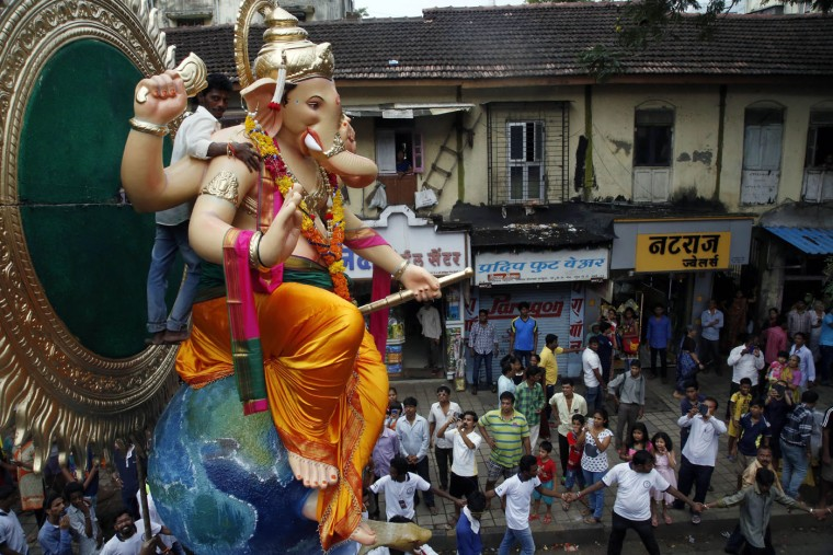 People watch as devotees transport an idol of elephant headed Hindu god Ganesha from a workshop to a worship venue ahead of the Ganesh Chaturthi festival in Mumbai, India, Sunday, Sept. 13, 2015. After worshipping during the ten day long festival, the idol will be immersed in the Arabian Sea. (AP Photo/Rajanish Kakade)