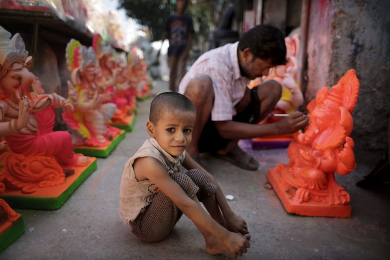 An Indian boy sits next to his father as he gives final touches to the idols of elephant headed Hindu god Ganesha in New Delhi, India, Wednesday, Sept. 9, 2015. The idols are in demand ahead of the Ganesh Chaturthi festival that celebrates the birthday of Lord Ganesha. (AP Photo/Altaf Qadri)
