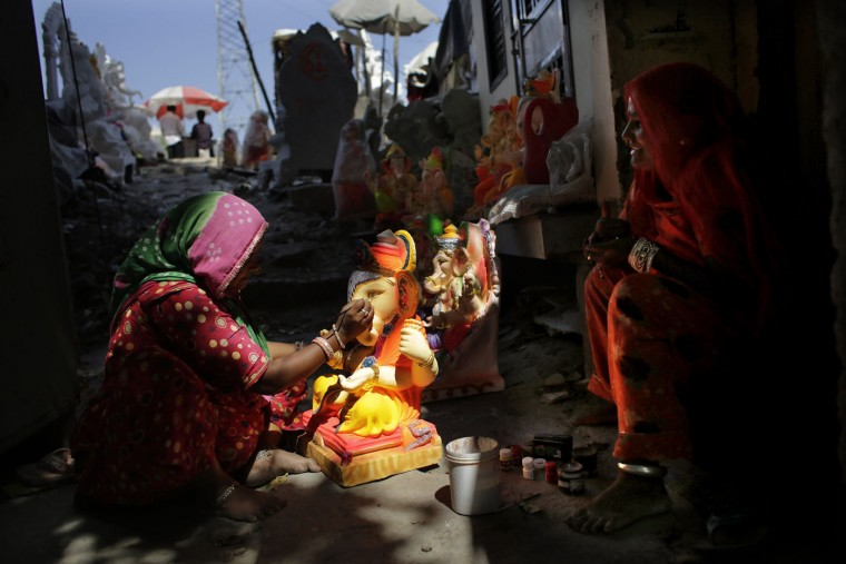 An Indian artisan gives final touches to the idols of elephant headed Hindu god Ganesha in New Delhi, India, Wednesday, Sept. 9, 2015. The idols are in demand ahead of the Ganesh Chaturthi festival that celebrates the birthday of Lord Ganesha. (AP Photo/Altaf Qadri)
