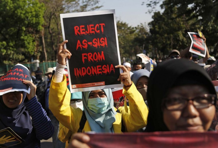 A student holds up a poster during a protest against Egyptian President Abdel-Fattah el-Sisi in Jakarta, Indonesia, Friday, Sept. 4, 2015. Dozens of students staged the protest against el-Sisi, who is currently on a visit in the country, accusing him of committing crimes against humanity.  || CREDIT: DITA ALANGKARA - AP PHOTO