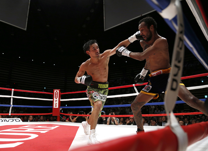 Japanese champion Shinsuke Yamanaka, left, sends a left to Panama's challenger Anselmo Moreno in the 12th round of their WBC bantamweight boxing title match in Tokyo on Tuesday. Yamanaka defended his title by a 2-1 decision. (Toru Takahashi/AP)