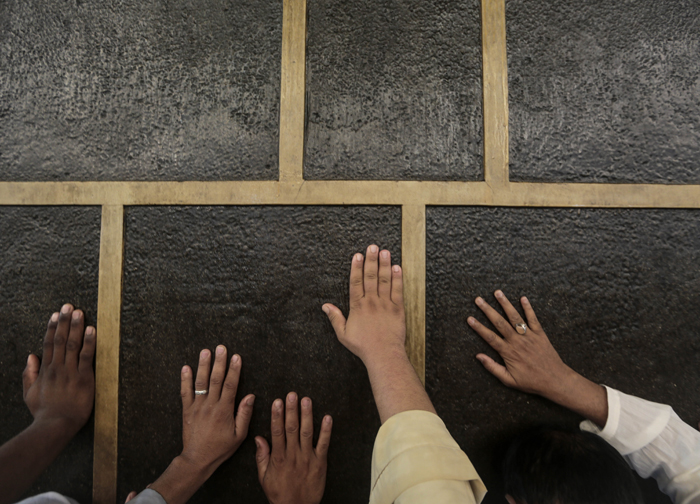 "In this Monday photo, Muslim pilgrims pray while touching the Kaaba, the cubic building at the Grand Mosque in the Muslim holy city of Mecca, while performing Tawaf, an anti-clockwise movement around the Kaaba and one of the main rites of the hajj, in Saudi Arabia. In Mecca, the holy site all the world''s Muslims pray toward, the annual hajj pilgrimage began Tuesday with over 2 million faithful gathering to call out in Arabic: ""Here I am, God, answering your call. Here I am."" (Mosa'ab Elshamy/AP)"