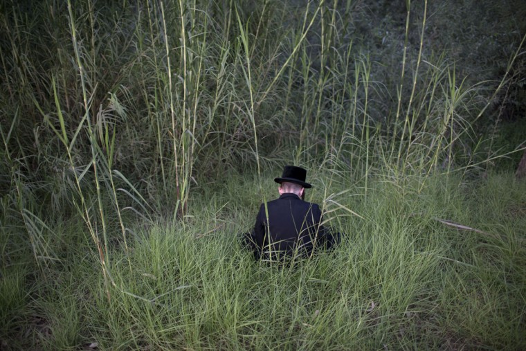 An ultra-Orthodox Jewish man prays by the Yarkon springs as he participates in a Tashlich ceremony near Rosh Haain, central Israel, Monday, Sept. 21, 2015. (AP Photo/Oded Balilty)