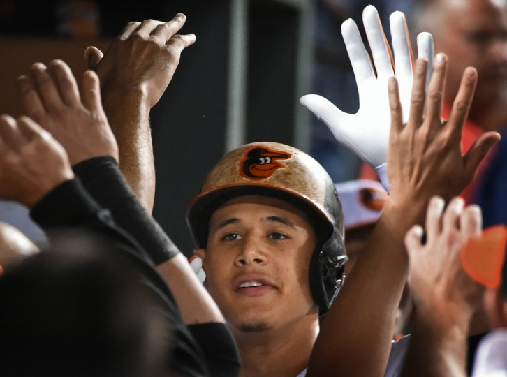 The Orioles' Manny Machado high fives teammates in the dug out after his go-ahead solo home-run against Red Sox in the fifth inning at Oriole Park at Camden Yards.  (Kenneth K. Lam/Baltimore Sun)
