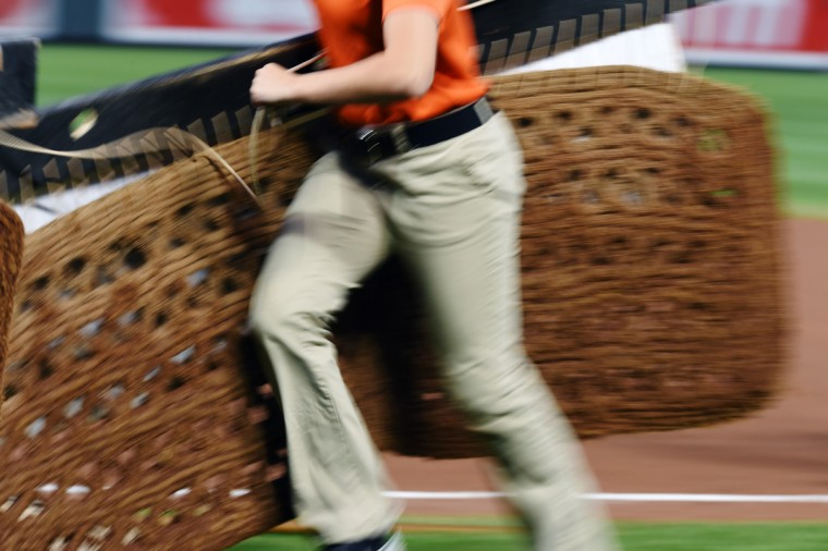 Orioles ground crew member runs off the field after smoothing the in-field during the seventh inning. (Kenneth K. Lam/Baltimore Sun)