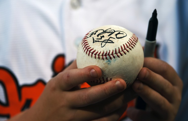 A young fan clutches a batting practice ball signed by Orioles' Steve Clevenger and Steve Pearce.  (Kenneth K. Lam/Baltimore Sun)