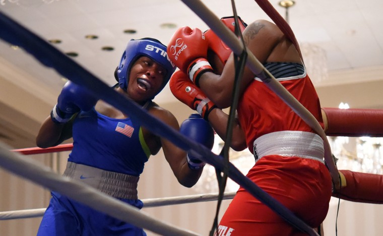 Franchon Crews, in blue, throws punches as Schmelle Baldwin of Wilmington, DE, as Baldwin covers up to deflect the blows during their quarter finals match at the Olympic Trials Qualifier II.  (Lloyd Fox/Baltimore Sun)