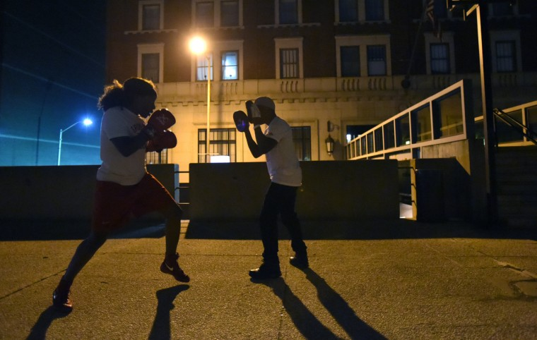 Franchon Crews spars with her husband, Glenn Dezurn Jr. under a street light outside of the Baltimore Harbor Hotel before her championship bout with Lesha Kenney.  The bout was the gold medal round of the Pathway to Glory Olympic Trials Qualifier II held at the Baltimore Harbor Hotel in Baltimore,Maryland. (Lloyd Fox/Baltimore Sun)