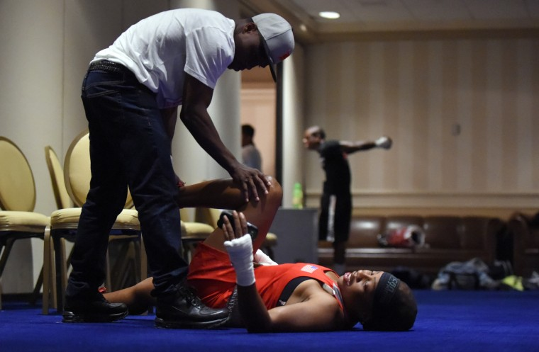 Franchon Crews stretches with the help of her husband and trainer, Glenn Dezurn Jr. prior to her gold medal bout with Lesha Kenney. (Lloyd Fox/Baltimore Sun)