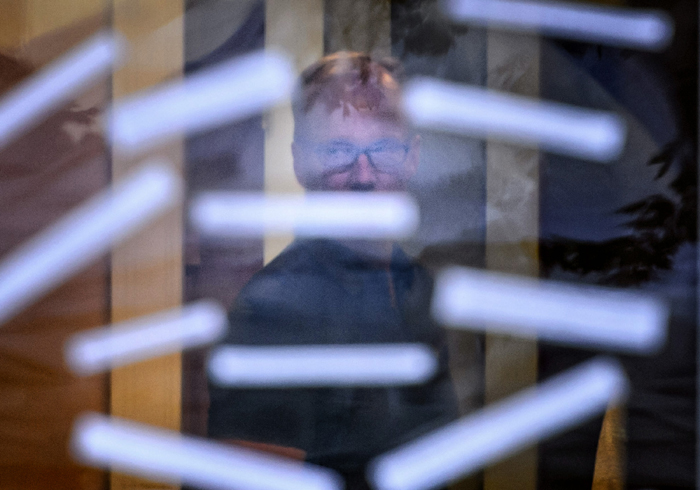 Dentist Walter Palmer looks back from his office through the front door, where protesters hung notes calling for his extradition, on Tuesday in Bloomington, Minn. A private security guard later removed the protesters. (Glen Stubbe/Minneapolis Star Tribune/TNS)