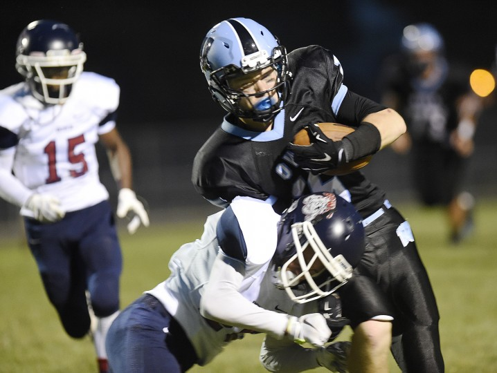 Westminster's Logan Nave is hit by Bowie's Lawrence Scott during the first half of Westminster's season opener against Bowie in Westminster Friday, Sept. 4, 2015. (Dylan Slagle/Carroll County Times)