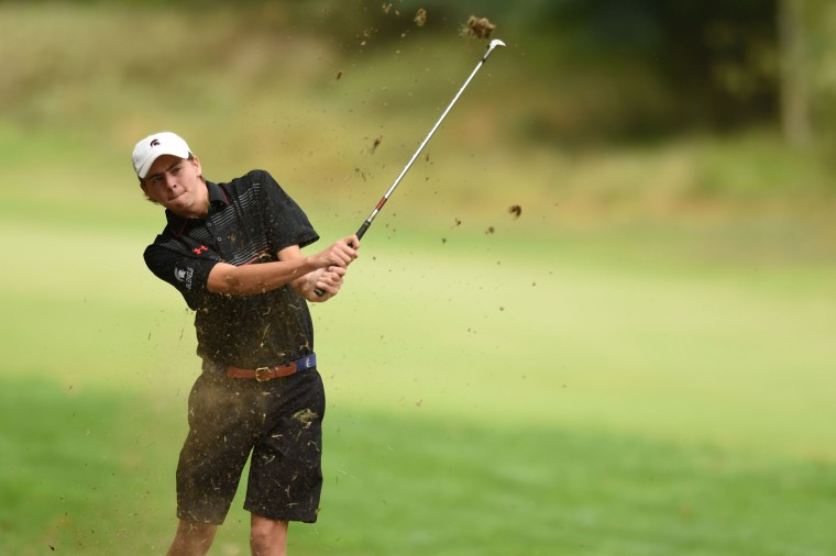 Glenelg's John McAuliffe kicks up a little dirt as he hits an approach shot from the rough on the fourth hole during at golf match between Marriotts Ridge, Glenelg and Wilde Lake at Fairway Hill Golf Club in Columbia on Tuesday, Sept. 22. (Brian Krista/BSMG)