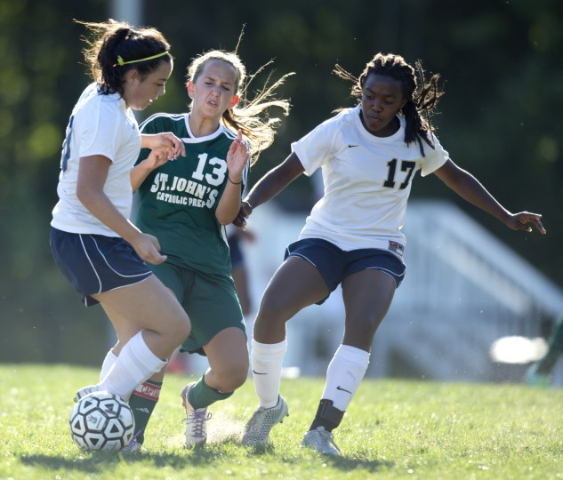 Chapelgate's Rachel Terry, left, and Jasa Curry, right, battle St. John's Abby Conway, center, for the ball during the girls soccer game at Chapelgate Christian Academy in Marriottsville, MD on Wednesday, September 23, 2015. (Jen Rynda/BSMG)