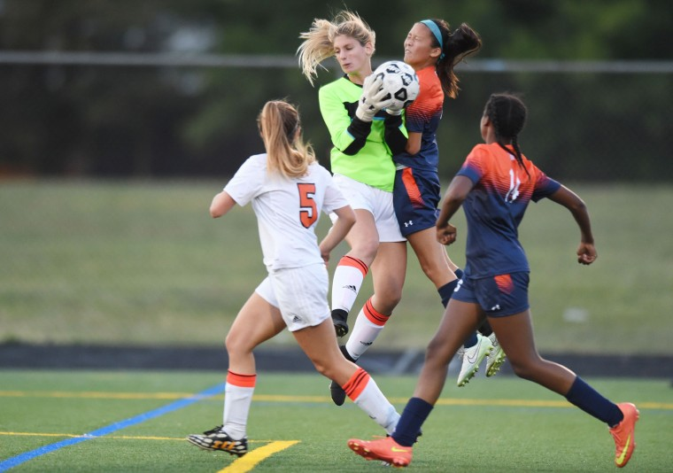 Oakland Mills goalie MaryJane Stockford secures the ball as she collides in mid-air with Reservoir's Cassidy Pham during a girls soccer game at Oakland Mills High School in Columbia on Thursday, Sept. 24. (Brian Krista/BSMG)