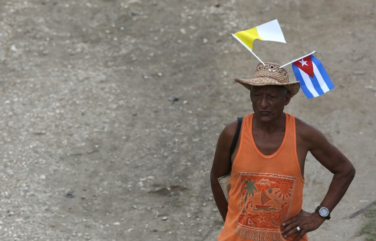 A man with Vatican and Cuban flags tucked into his hat waits for the arrival of Pope Francis in Havana, Cuba, Saturday, Sept. 19, 2015. Pope Francis begins a 10-day trip to Cuba and the United States on Saturday, embarking on his first trip to the onetime Cold War foes after helping to nudge forward their historic rapprochement. (Enric Marti/Associated Press)