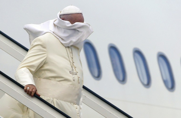 A gust of wind blows off Pope Francis' mantle as he descends from the plane upon his arrival at Jose Marti international airport in Havana on September 19, 2015. Pope Francis on Saturday urged the United States and Cuba to pursue their nascent reconciliation as he arrived in Havana on the first leg of a high-profile trip that will also take him to the US. (Pool/Tony Gentile/AFP-Getty Images)
