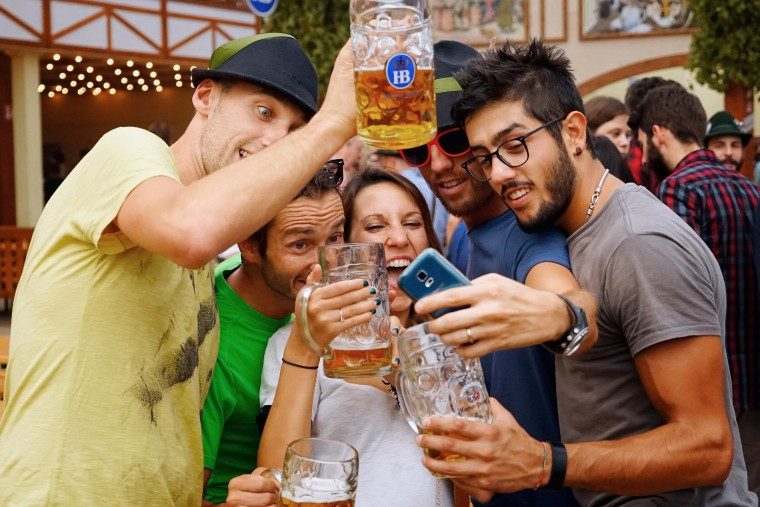 Revelers take photos as they drink beer at Hofbraeuhaus beer tent on the opening day of the 2015 Oktoberfest on September 19, 2015 in Munich, Germany. The 182nd Oktoberfest will be open to the public from September 19 through October 4and will draw millions of visitors from across the globe in the world's largest beer fest. (Johannes Simon/Getty Images)